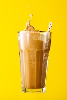 Tasty fresh iced creamy latte coffee splash straw in glass on yellow vivid background. Closeup.