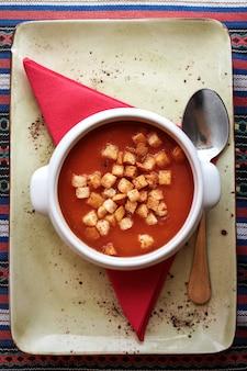 テーブルにスプーンで白いセラミックボウルにcroutonsとおいしい新鮮なトマトスープ。