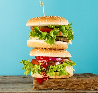 Tasty unhealthy burgers on wooden board on blue bright background, ready to eat or serve. Bright background. Selective focus.