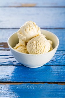 Tasty vanilla ice scoops in bowl on blue wooden rustic table. Closeup.