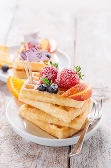 Tasty waffles with different pieces of fruit
