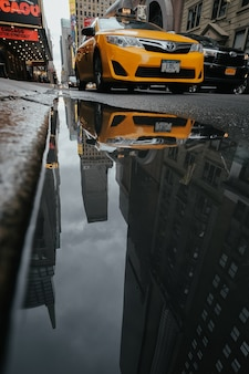 Taxi reflected in a puddle