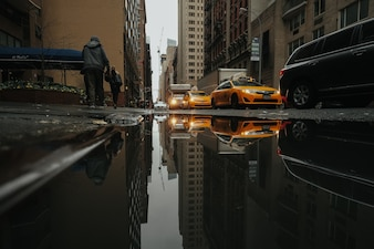 Taxis reflected in a puddle of water