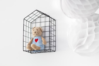 Teddy bear in a cage