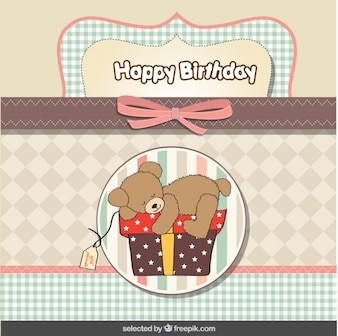 Teddy bear on present birthday card in pastel colors