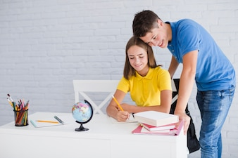 Teen boy helping his girlfriend to study