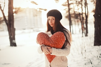 Teen holding her heart-shaped cushion outdoors