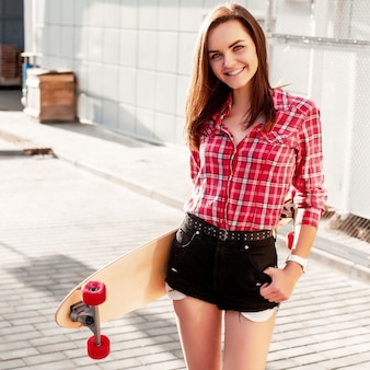 Teen with black shorts holding a skateboard