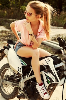 Teen with hand on chin sitting on the motorbike