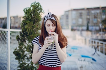 Teenage girl drinking from a glass with a straw