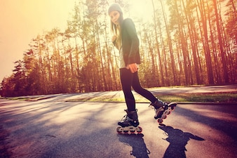 Teenage girl on roller skates at summer.