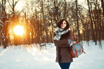 Teenage girl standing with her handbag in a snowy forest