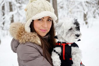 Teenager enjoying with her dog a day in the snow