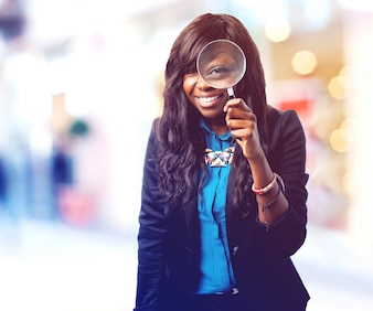 Teenager holding a magnifying glass with her left hand