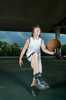 Teenager playing basketball