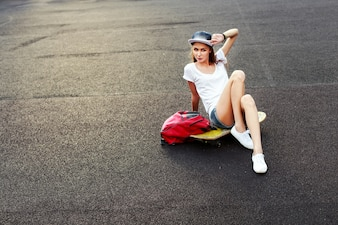 Teenager sitting on skateboard with a hand touching his cap