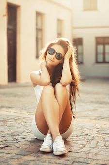 Teenager with sunglasses sitting on the floor