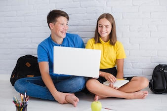Teenagers laughing and using laptop