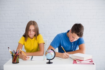 Teenagers making notes at lesson