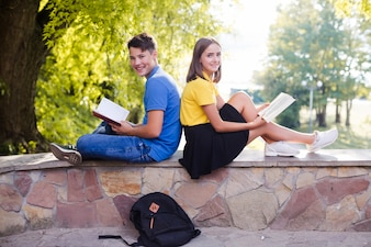 Teenagers with books in park
