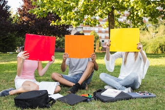 Teens covering faces with papers