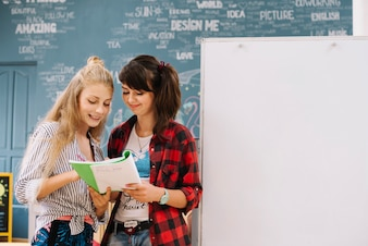 Teens reading book at whiteboard