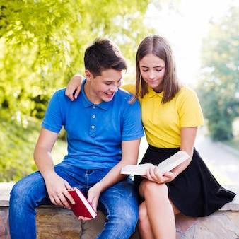 Teens reading books outside