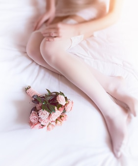 Tender pink bouquet lies before bride's knees on soft bed