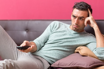Tensed Young Man Changing TV Channel at Home