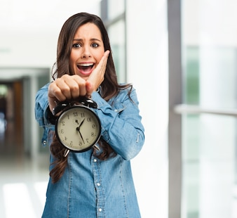 Terrified girl holding a clock
