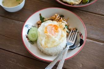 タイの炒めた鶏肉とバジルは、米と揚げた卵、タイのお気に入りの食べ物を提供しました。