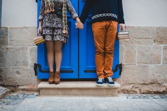 The boyfriend and girlfriend stand  on the stairs near building