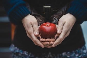 恋人のカップルは赤いリンゴを保つ