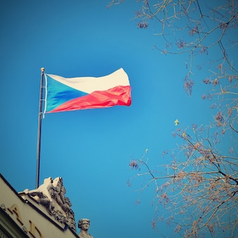The flag of the Czech Republic on a building with blue sky and the sun in the background.