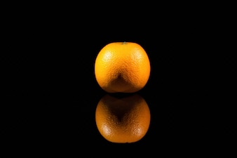 The orange stands on the black background
