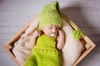 The small baby has a dummy and  lies in the basket
