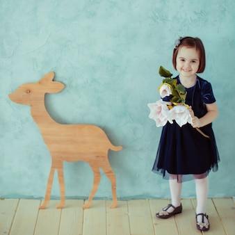 小さな女の子は花を保ち、鹿の近くに立つ