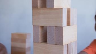 スタックゲームをしている子供の手で木製のブロックからの塔