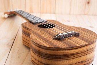 The ukulele on wooden background