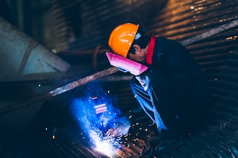The welder in the machinery works is doing the welding work