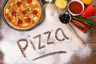 The word pizza written in flour