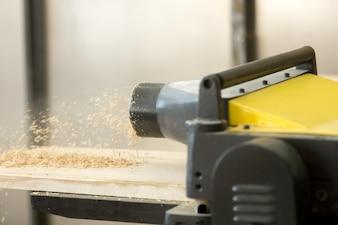 Thickness planer machine in woodworking workshop