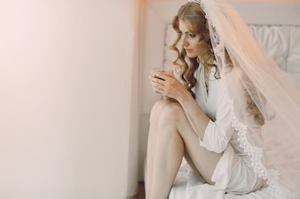 Thinking bride with a cup