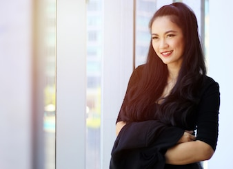 Thoughtful and happy asian businesswoman looking through window in office
