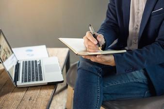 カフェで働くペンで木製のテーブルのノートにノートパッドを持っているカジュアルなシャツの思慮深い若いビジネスマン