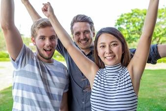 Three cheerful multiethnic friends raising hands