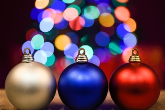 Three christmas balls on dark wooden board with bokeh in the background