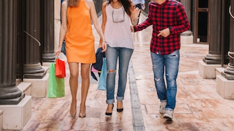 Three friends shopping in city