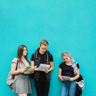 Three students with books on blue