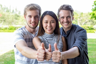 Three successful student friends showing thumbs up